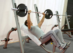 Trainer showing feet placement on the Incline Bench Press